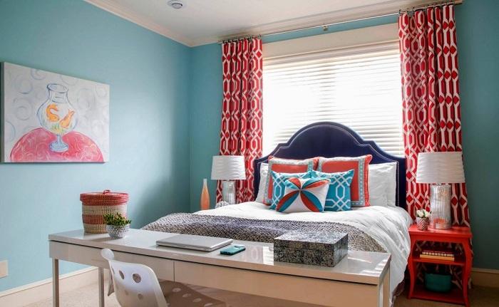 Интересное оформление спальной с голубыми стенами и оригинальными алыми шторами.