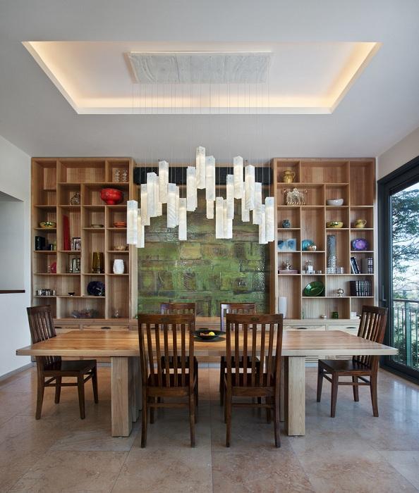 Множество деревянных элементов интерьера дополнены прекрасной люстрой над столом.