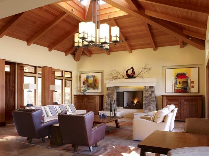 Красивое оформление гостиной с деревянным потолком, в центре, которого мансардное окно, что дополняет общую обстановку.