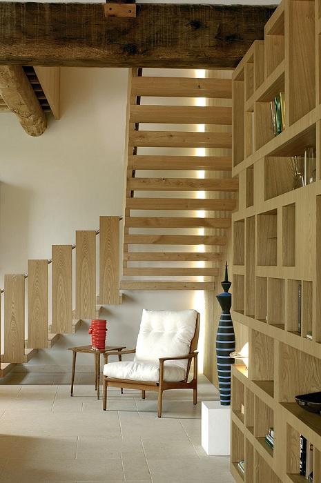 Светлая комната украшена деревянной лестницей в Средиземноморском стиле.