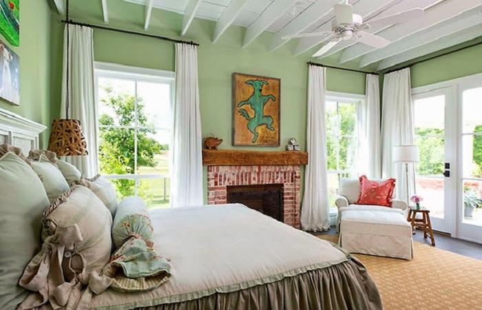 Уютная спальня в мятно-зеленых тонах с большой кроватью и шикарными окнами.