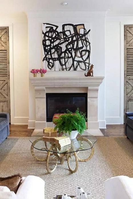 Оформление гостиной с камином, картиной и не менее привлекательным столиком.