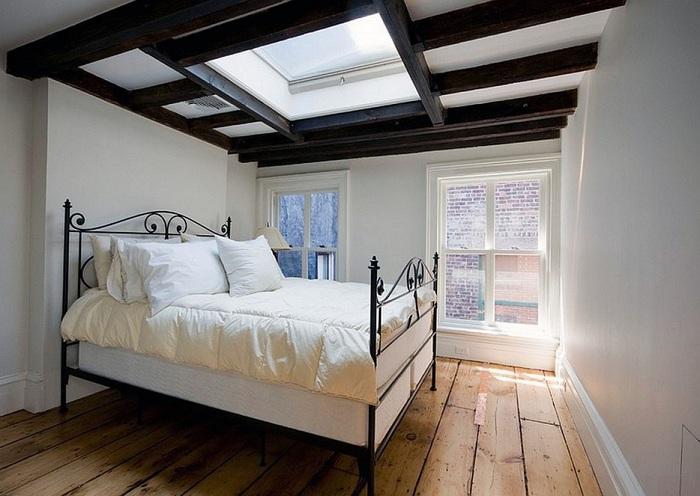 Уютная спальная комната с прекрасным мансардным окном и шикарным потолком, дополняют интерьер комнаты.
