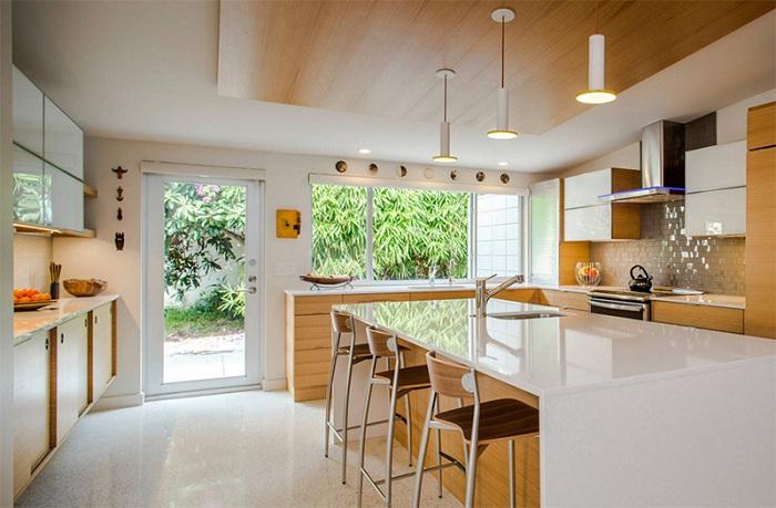 Просторная кухня, которая сочетает в себе дерево и белый цвет.