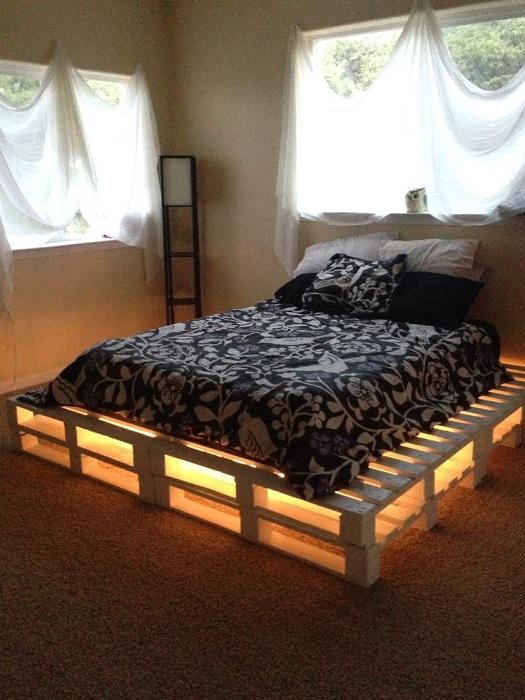 Симпатичный вариант оформления спальной с кроватью из паллет с необычной подсветкой.