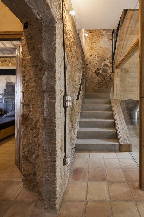 Интересный дизайн комнаты с необычными каменными стенами дополнен лестницей в Средиземноморском стиле.