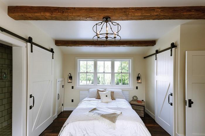 Белоснежная спальня с шикарным окном и множеством дверей очень гармонично вписалась в интерьер дома.