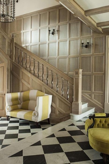 Комната с лестницей в шикарном ореховом цвете, дополнена яркими желтыми креслами - для прекрасного настроения.