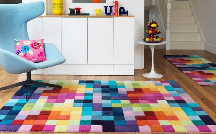Яркий напольный ковер создает положительную атмосферу в комнате.