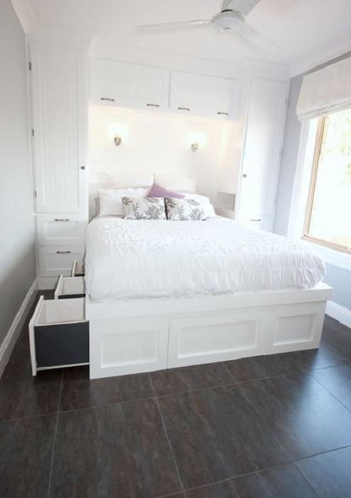 Красивая белоснежная спальня с интересными ящиками в кровати, то что порадует и оптимизирует пространство.