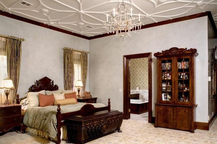 Богатое оформление спальни в светлых тонах с белыми узорами на потолке.