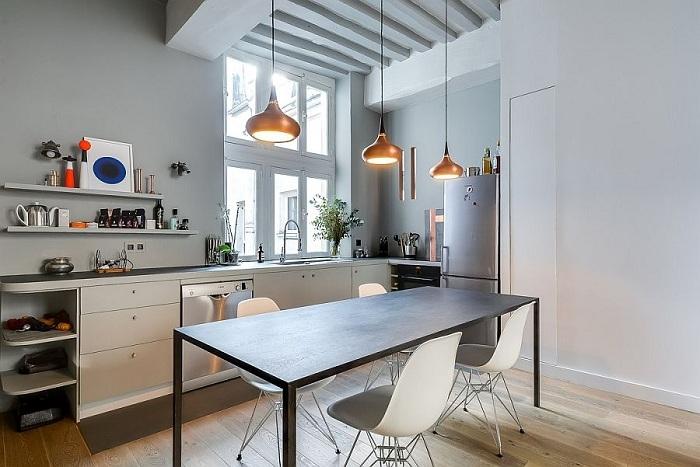 Стильний приклад оформлення кухні в сучасних мотивах з золотими креативними люстрами.
