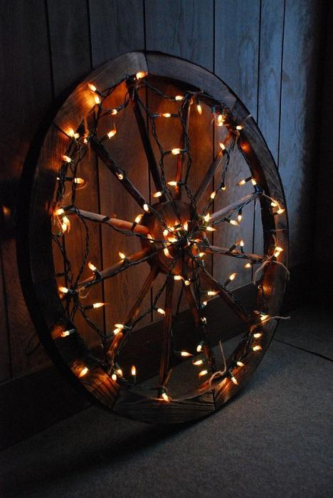 Нестандартное рождественское украшение - это колесо, которое украшено яркими огоньками.