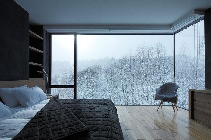 Спальня в черно-белых тонах с отличным видом на заснеженные деревья заставит погрузиться в мир фантазий и отдыха.