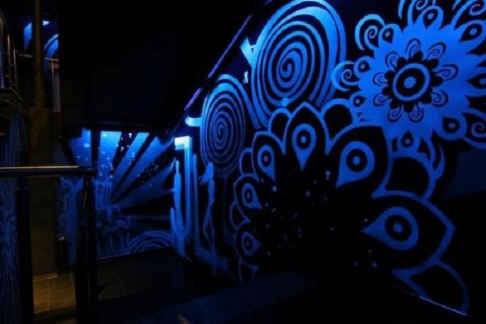 Интересный синий светящийся узор на стене порадует глаз и создаст интересную обстановку в комнате.