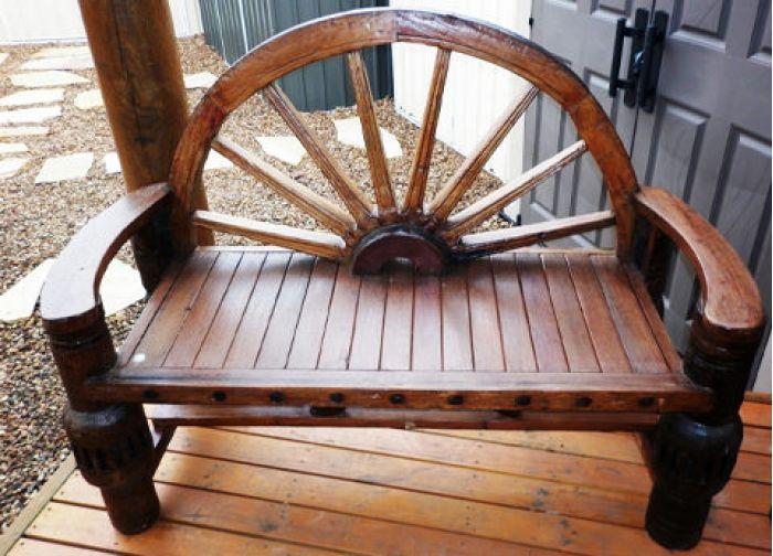 Удобная скамейка выполнена с элементом колеса украсит любое крыльцо около дома.