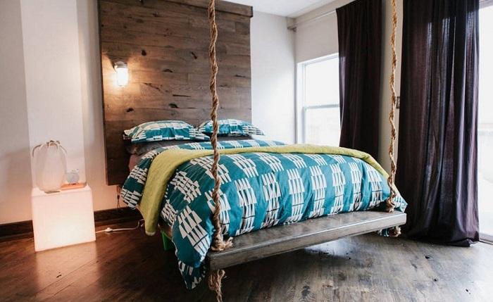 Оригинальный интерьер спальной с подвешенной кроватью и темными шторами.