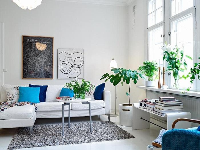 Белая цветовая схема этой маленькой гостиной отражает естественное освещение в комнате.