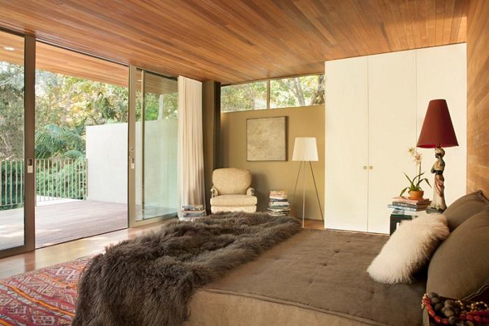 Красивая спальня в кофейных тонах со стеклянной дверью, которая создаст еще больше пространства.