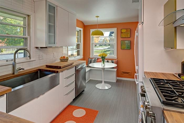 Кухня с яркими оранжевым декором, что увеличивает пространство.