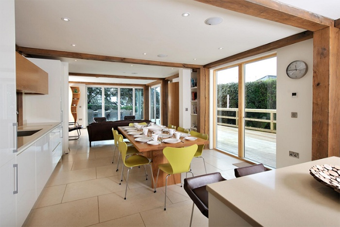 Красивая столовая несмотря на простой дизайн, украшена стульями зеленого цвета, что добавляют особенного вкуса и стиля.
