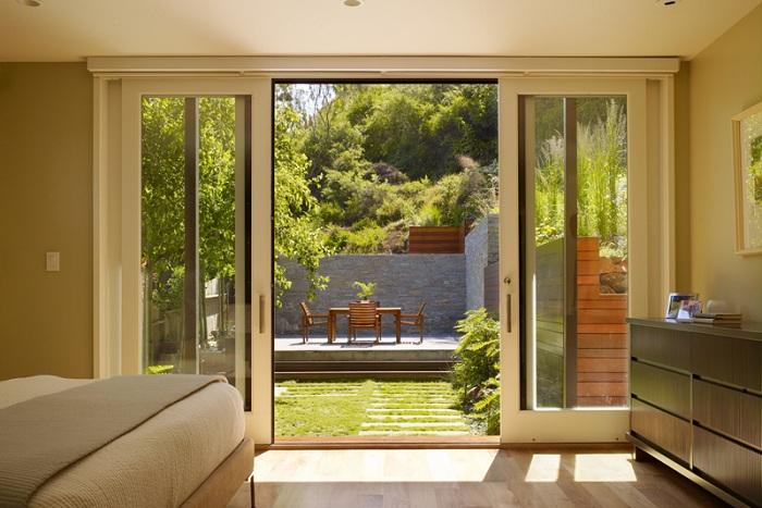 Прекрасный интерьер комнаты отлично сочетается с видами, которые открываются за её стеклянными раздвижными дверьми.
