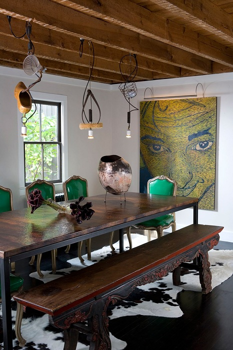 Интересный интерьер с деревянной скамьей и стильными кожаными зелеными стульями, что украшают столовую.