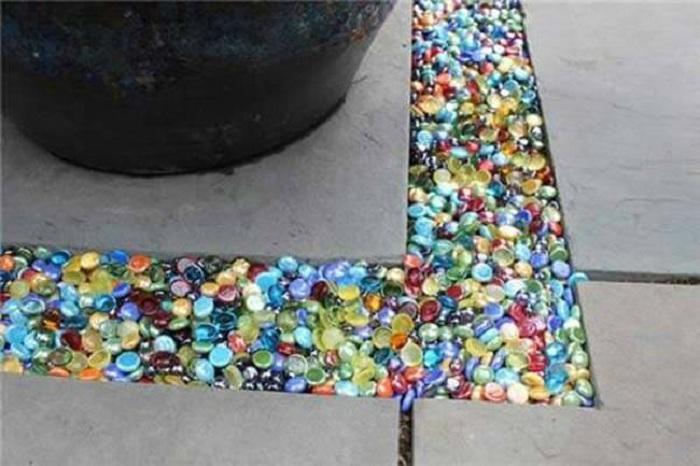Цветное стекло используется для заполнения зазора между брусчаткой, что в свою очередь делает её симпатичной и яркой.