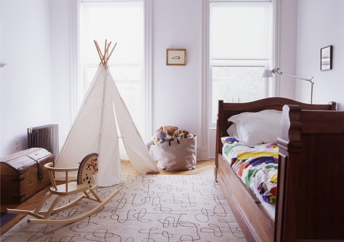 Комната в белых тонах, дополнена деревянными элементами и вигвамом.
