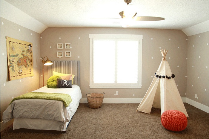 Спальня с вигвамом, который украшен помпонами.