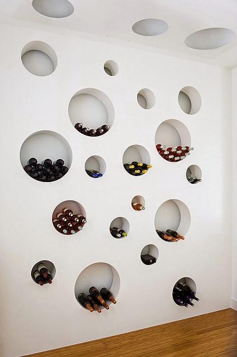 Удачный вариант хранения вина в круглых ячейках в стене, что смотрится очень интересно.