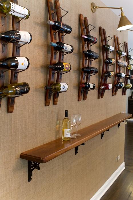 Нестандартный вариант облагородить стену за счет размещения на ней полок для вина.