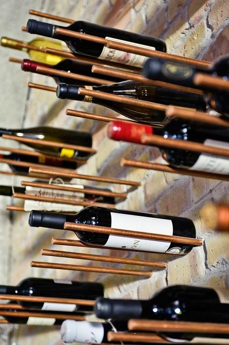 Симпатичный и нестандартный вариант для хранения вина - железные штыри в стене.