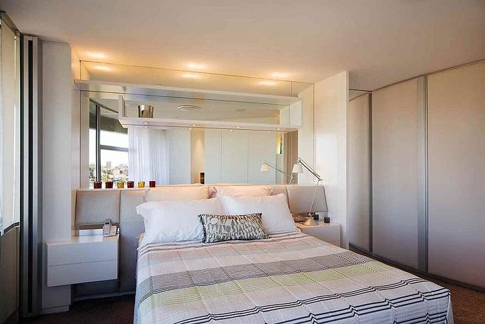Симпатичная спальня в светлых тонах с большим зеркалом на стене, по всей ширине комнаты.