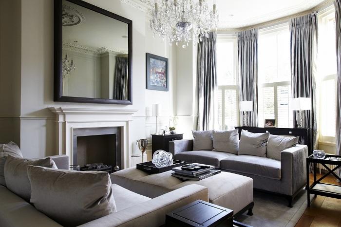 Нежная гостиная комната выполнена в светлых тонах и дополнена зеркалом на стене и шикарной люстрой.