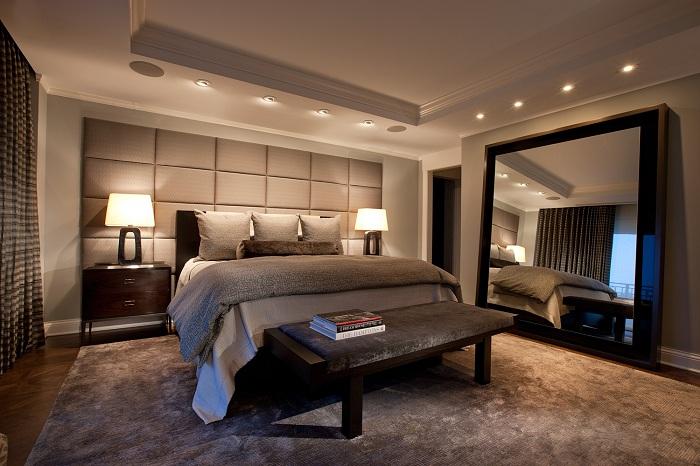 Уютная и теплая спальная комната в бежево-серых тонах с прекрасным зеркалом на стене.