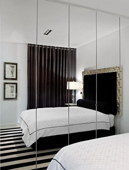 Отличное сочетание черно-белых классических цветов в интерьере комнаты с большим зеркалом на стене, что позволяет расширить рамки комнаты и создать необычную атмосферу.