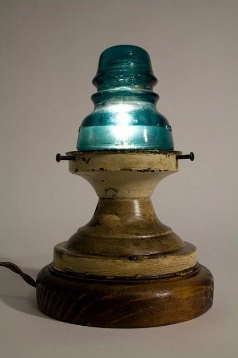 Деревянное основание и стеклянный электрический изолятор образуют настольную лампу.