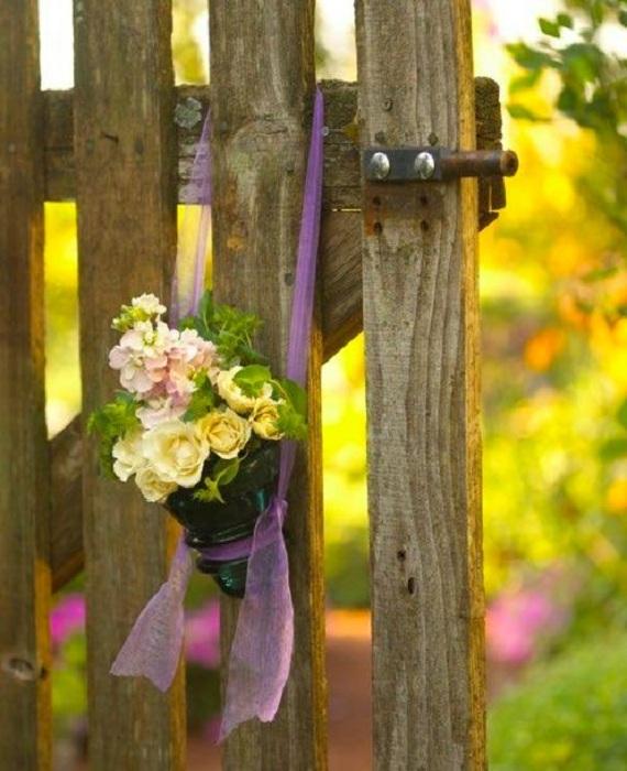 Интересное оформление подвесной вазочки для цветов из стеклянного изолятора, украсит атмосферу около дома.