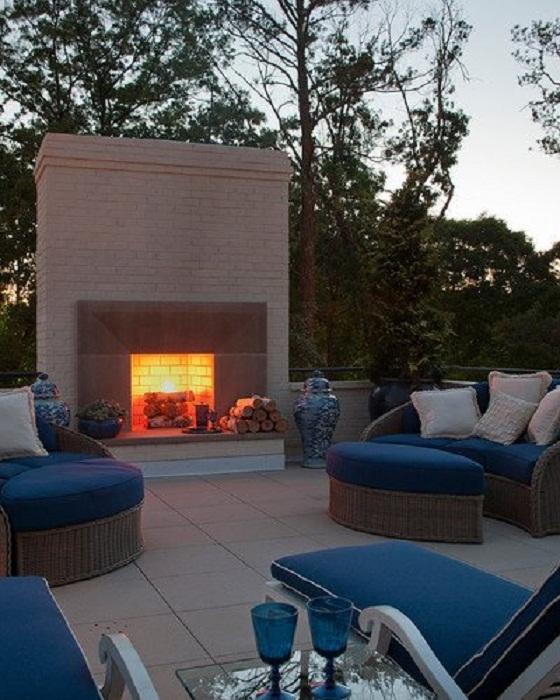 Точно понравится размещенный камин во дворе рядом с оригинальными диванчиками.