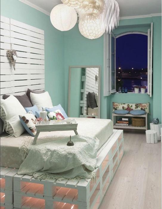 Интересная кровать на паллетах с нежным и спокойным фоном стен в комнате.