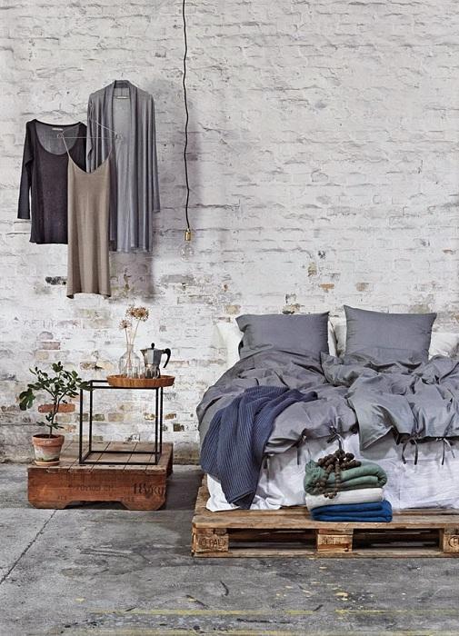 Сырой промышленный лофт с кирпичными стенами, цементным полом и каркасной кроватью с паллет.