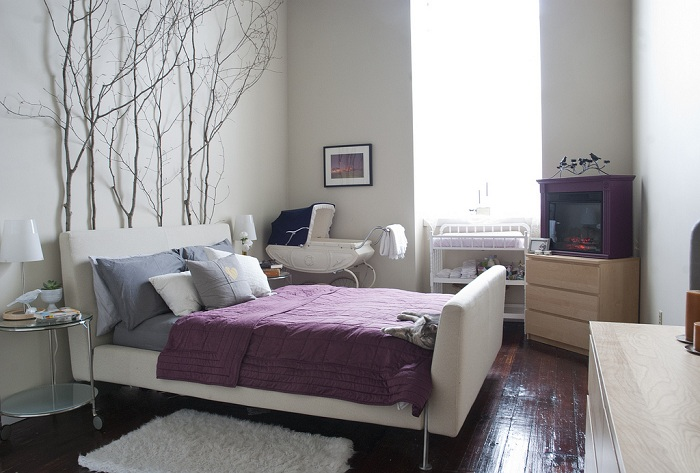 Изголовье кровати оформлено ветками, которые отлично сочетаются с интерьером.