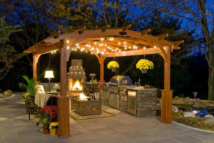 Беседка с полностью открытой кухней и камином, выполнена в форме арки.
