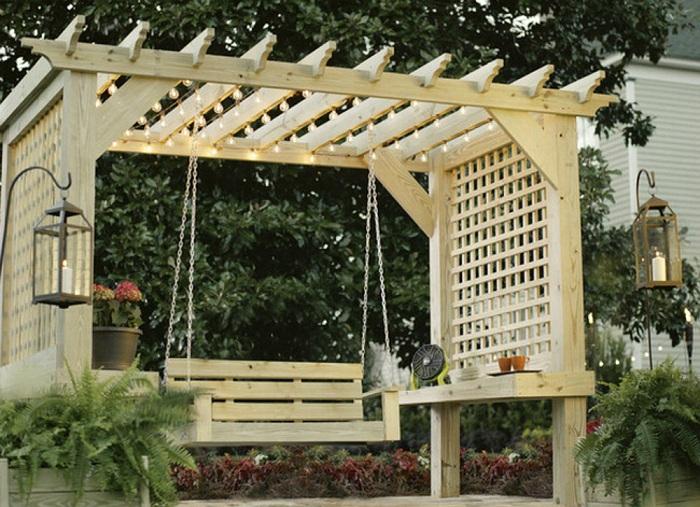 Деревянная конструкция перголы с качелей и боковыми решетками, которые защищают от посторонних взглядов.