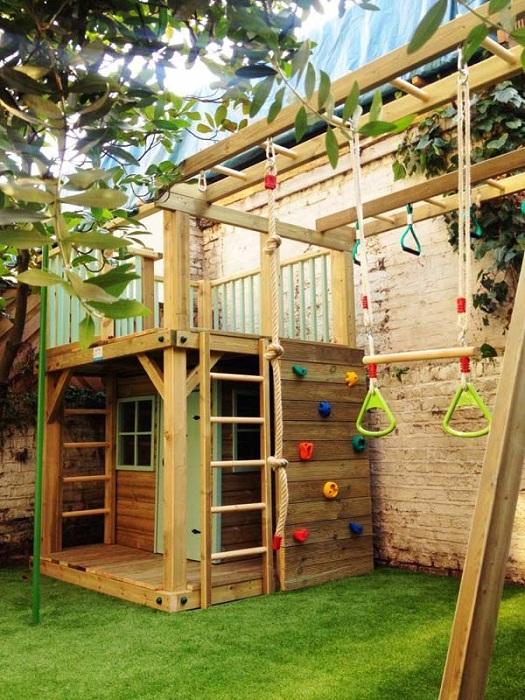 Яркий деревянный домик с игровой площадкой около него.