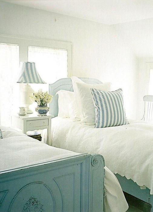 Интересная светлая обстановка в спальной с преобладающим белым цветом в оформлении.