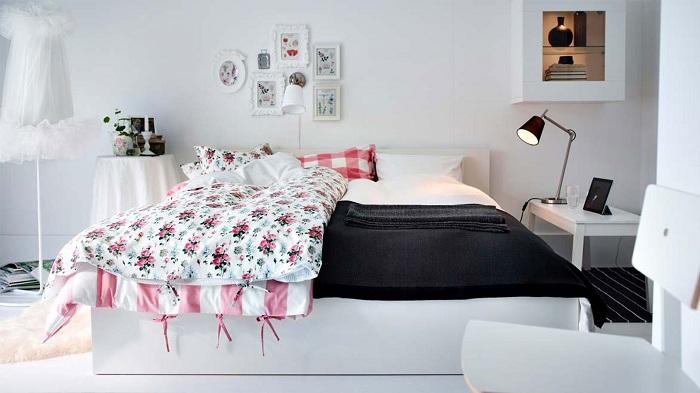 Интерьер с белоснежными стенами дополнен цветными принтами и черным одеялом - интересные акценты.