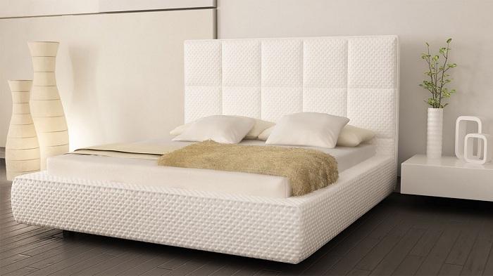 Белый интерьер спальни слегка разбавлен телесными тонами в оформлении декора.