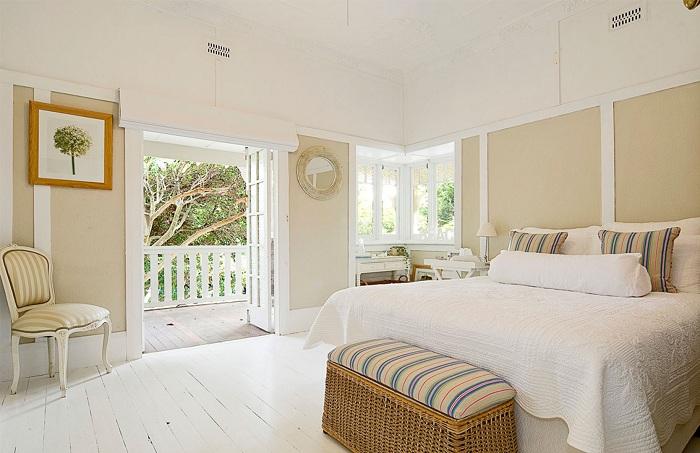 Красивый и светлый интерьер спальной в светлых тонах дополняют полосатые элементы интерьера.